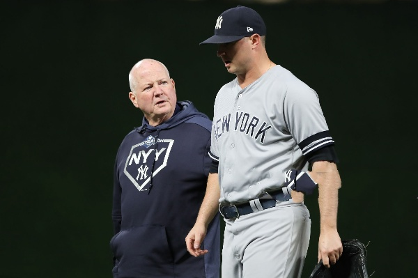 Pitcher James Paxton leaving the mound with a coach during ta Yankees game.