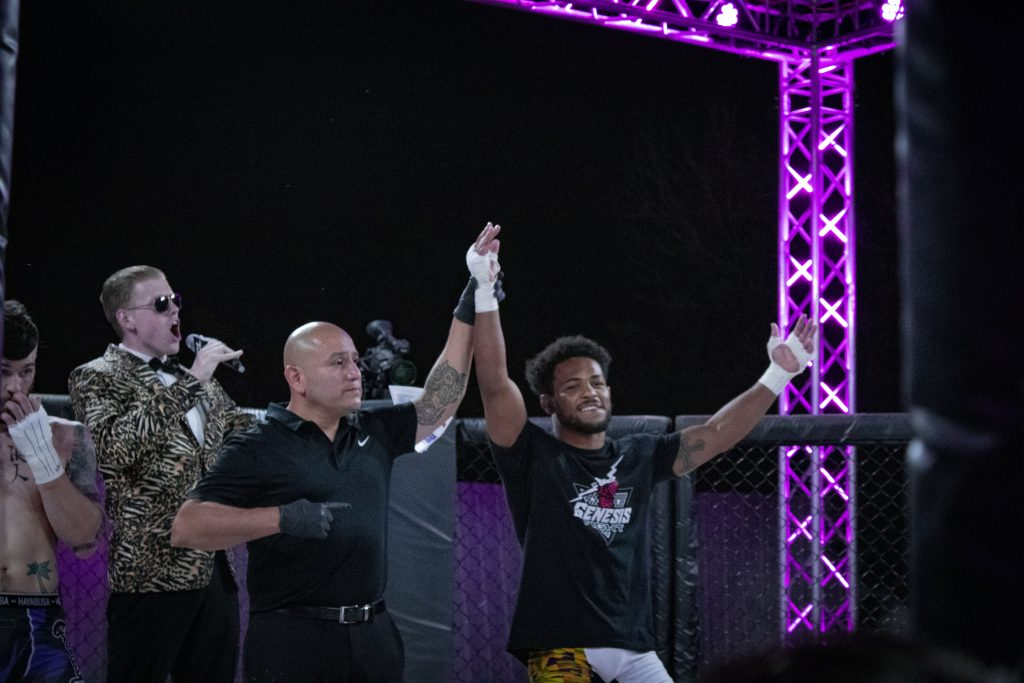 Sparta Welterweight Champion winner Archie Colgan getting his hand raised after winning. Photo credit Ashlee Moreno.